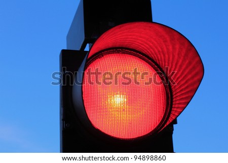 Red traffic light against a bright blue sky - stock photo