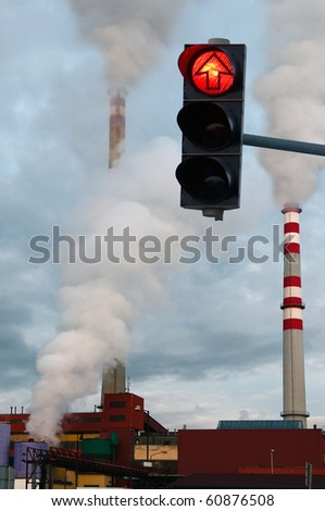 red traffic light and three smoking chimneys in the background - stock photo