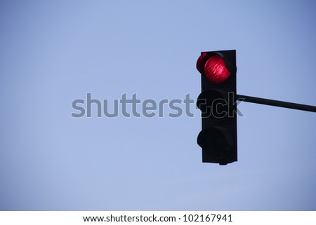 red traffic light in front of blue sky - stock photo