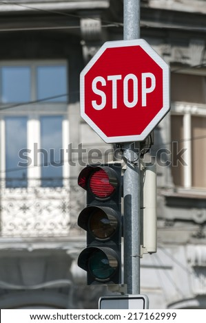 Red traffic light on and stop sign. - stock photo
