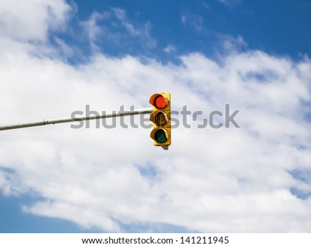 Red traffic light on cloud sky background. Photo. - stock photo