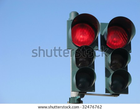 Red traffic light on sky - stock photo