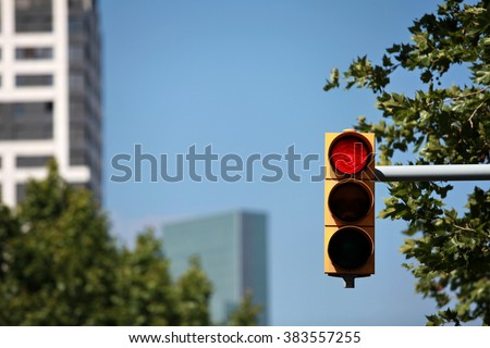 red  traffic light on the background of the skyscraper - stock photo