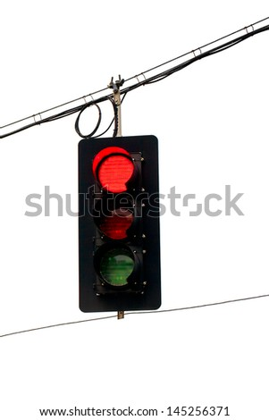 Red traffic light swinging from wires overhead. Close up with white background.  Vertical - stock photo