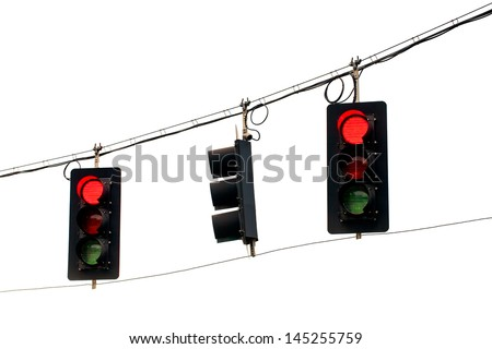 Red traffic lights swinging from wires overhead. Close up on white background. - stock photo