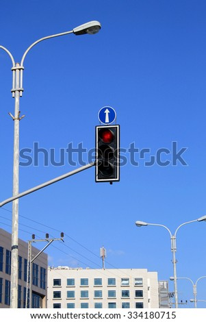 Red traffic lights with arrow against blue sky background - stock photo