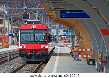 Red Train locomotive coming to Interlaken platform Station Switzerland - stock photo