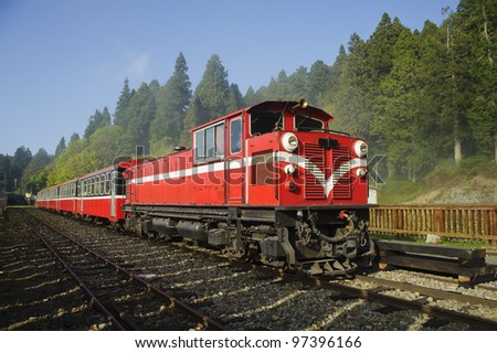 Red train under blue sky on railway forest in Alishan National Scenic Area, Taiwan, Asia. - stock photo