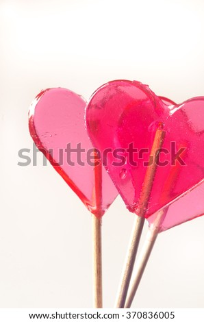 red transparent heart shaped lollipops - stock photo
