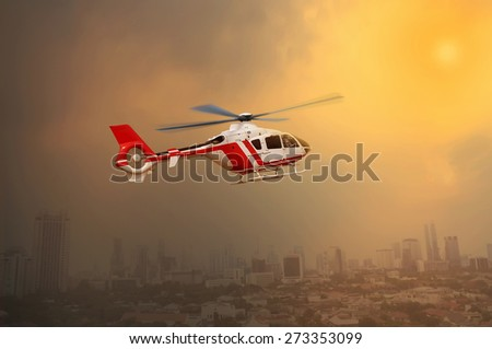 Red transport helicopter flying with city view in the afternoon - stock photo