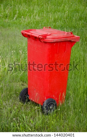 red trashcan on green summer  resort  grass with black wheels - stock photo