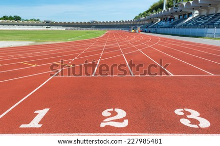 Red treadmill at the stadium with the numbering. - stock photo