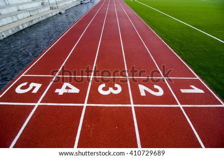 Red treadmill at the stadium with the numbering from one to five - stock photo