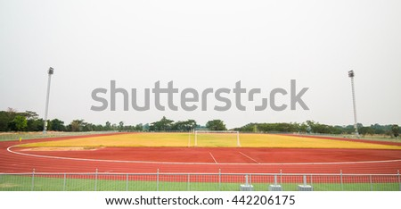 Red treadmill, track running and football field at the stadium with  grass. - stock photo