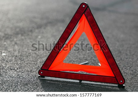 Red triangle of a car on the road