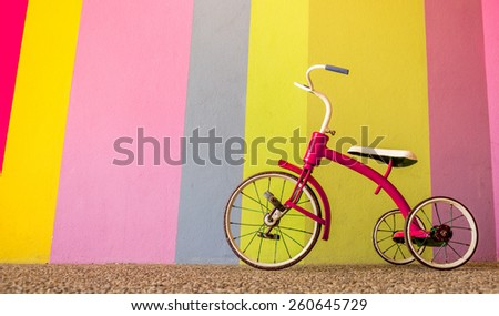 Red Tricycle In Front Of Colorful Wall - stock photo