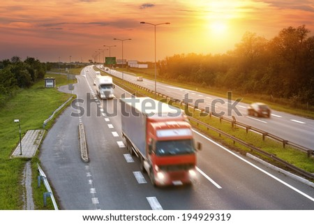 Red truck in the rush hour on the highway at dusk - stock photo