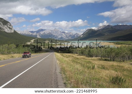 Red Truck on a Winding Highway Next to a Mountain Lake in the Kootenay Plains - Alberta, Canada - stock photo