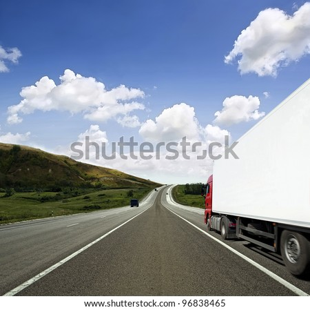 Red truck on asphalt road over blue cloudy sky background - stock photo
