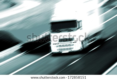Red truck on blurry asphalt road over blue cloudy sky background  - stock photo