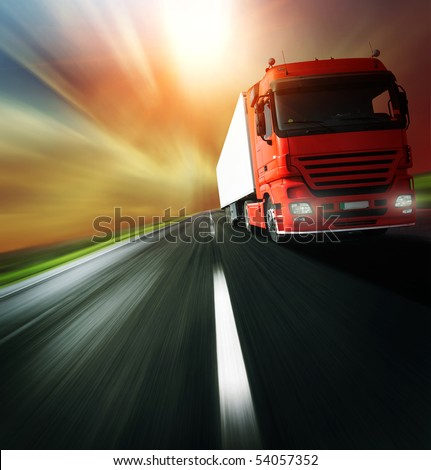 Red truck on blurry asphalt road over cloudy sky background - stock photo