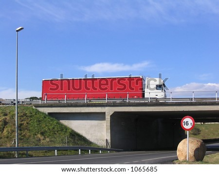 Red truck on the road crossing a bridge - stock photo