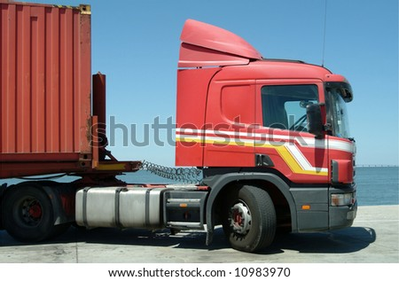 Red truck with cargo container in port - stock photo
