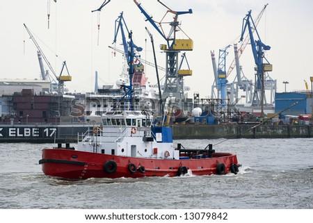 red tugboat on Elbe river at Hamburg harbor - stock photo