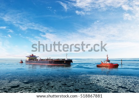 Red tugboat towing a tanker ship at winter.