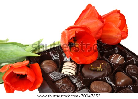 Red tulips and box of chocolate candy - stock photo