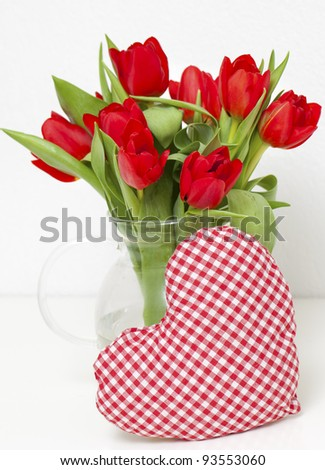 red tulips and heart-shaped pillow - stock photo