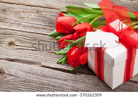 Red tulips and Valentine's day gift box on wooden table. View with copy space