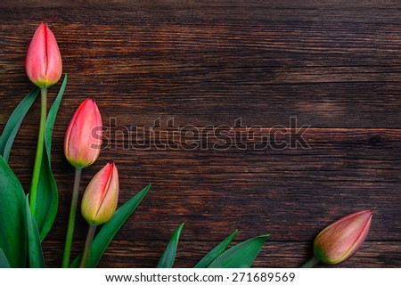 Red tulips flowers bouquet on old wooden table background. Top view with copy space. - stock photo