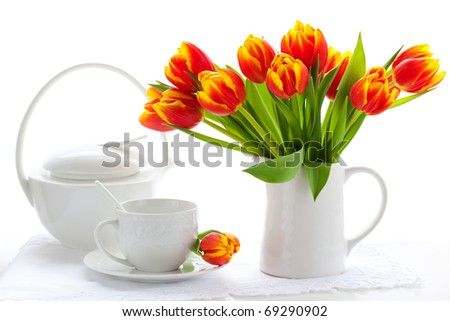 red tulips in a jug and cup of tea on white - stock photo
