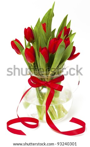 red tulips in a vase with a red ribbon isolated on white