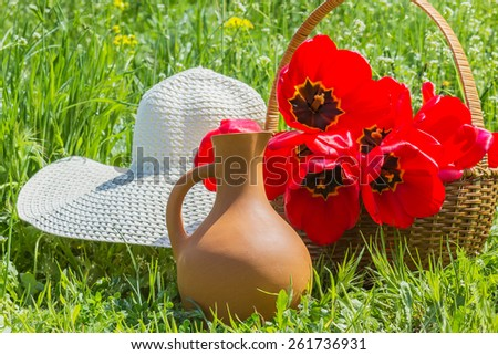 Red tulips in a wicker basket, white hat and crock in the green grass on a sunny spring day - stock photo