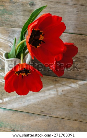 Red tulips on the old wooden table