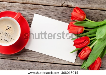 Red tulips, Valentines day greeting card and coffee cup over wooden table. Top view with copy space - stock photo