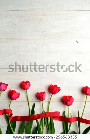 Red tulips with ribbon on white wooden background - stock photo