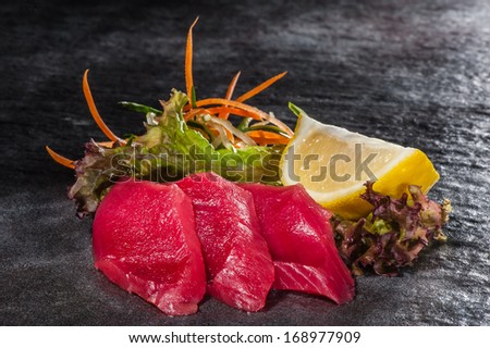 Red tuna slices with vegetable salad and lemon - stock photo