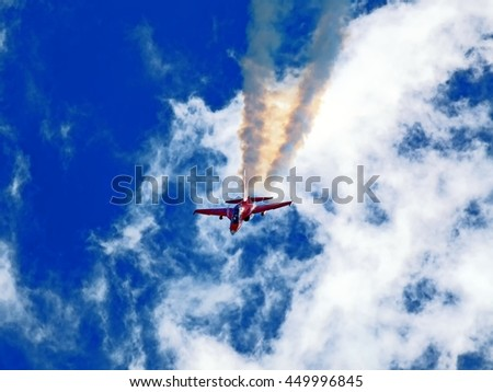 red twin jet engine twin seater trainer combat aircraft performing aerobatic maneuver with massive jet engine smoke against dramatic cloudy sky detail exterior action view - stock photo
