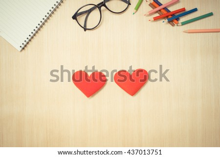 Red two hearts on artist table with color pencil and notebook. Retro filter. - stock photo