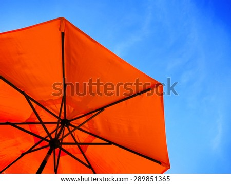 Red umbrella and blue sky symbolizing vacationing in summer - stock photo