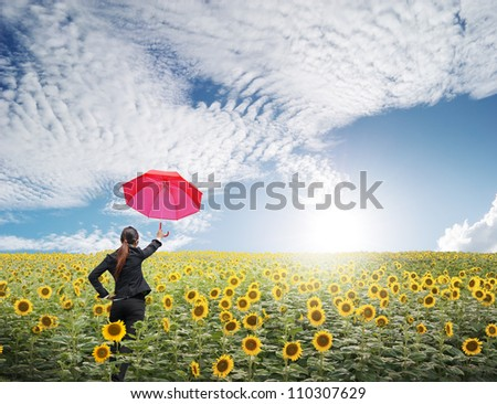 Red umbrella Business woman standing in blue sky over sunflowers field - stock photo