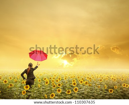 Red umbrella Business woman standing in sunset over sunflowers field - stock photo