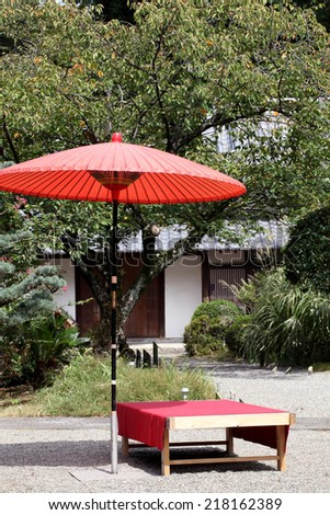 red umbrella in garden for green tea ceremony - stock photo
