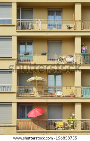 Red umbrella - Parasols on the balconies of a tall apartment building in France - stock photo