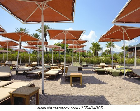 Red Umbrellas and Empty Loungers on a tropical sand Beach  - stock photo