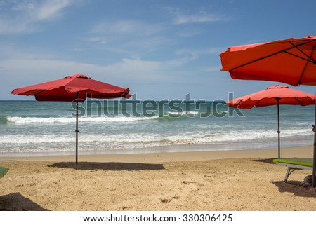 Red umbrellas on the beautiful beaches of Dakar with the waves of the Atlantic ocean in the background - stock photo