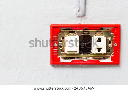 red uncovered electrical outlet switch on grey wall - stock photo